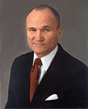 Raymond W. Kelly is seen here wearing a handkerchief in his left-breast pocket.  This is  a very common addition to a suit.
